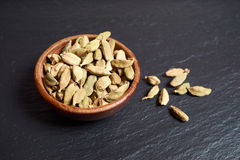 Cardamom on slate platter. Whole green cardamom capsules in a brown wooden bowl on a black slate platter Stock Photography