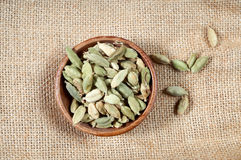 Cardamom in wooden bowl. Wooden small bowl with whole green cardamom seeds Royalty Free Stock Images
