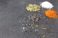 Cardamomo, açafrão, caril, pimenta, sal em um backgrou de pedra preto Foto de Stock