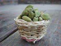 Cardamomos en la cesta de bambú en el tablero de madera Foto de archivo libre de regalías