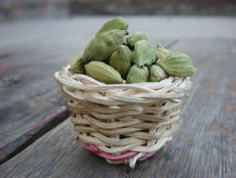 Cardamom in bamboo basket on wooden board. Green cardamom in bamboo basket on wooden board Royalty Free Stock Photo