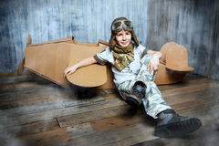Cardboard airplane. Little dreamer boy playing with a cardboard airplane. Childhood. Fantasy, imagination Stock Photo