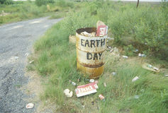 Cardboard beer cartons on the ground next to a trash can with the words �Earth Day� painted on its side Royalty Free Stock Photography