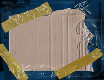 Cardboard on blue grunge background. Torn piece of cardboard taped to a blue grunge background Royalty Free Stock Images