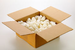 Cardboard box. A cardboard box with yellow packing styrofoam peanuts, isolated on white background Royalty Free Stock Photo