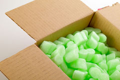 Cardboard box. A cardboard box with green packing styrofoam peanuts Stock Photos
