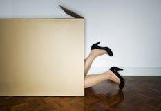 Cardboard box. Woman hiding in cardboard box Royalty Free Stock Photos