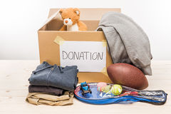 Cardboard box with donation clothes and different objects on white Royalty Free Stock Image