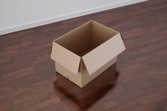 Cardboard box in empty room with dark floor. 3d rendering of a cardboard box in a empty room with dark wood floor Royalty Free Stock Photo