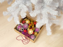 Cardboard box full of various Christmas decorations and a bead garland Royalty Free Stock Photo