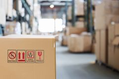 Cardboard box with goods on the background of a blurry modern warehouse. Cardboard box with goods in warehouse Royalty Free Stock Photography