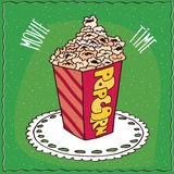 Cardboard box with a heap of popcorn. Bright cardboard box with a heap of popcorn, lie on lacy napkin. Green background and lettering Movie time. Handmade Stock Image