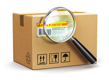 Cardboard box parcel with tracking number and magnifying glass. Creative abstract global logistics, worldwide shipping, delivery and online internet order parcel Royalty Free Stock Photography