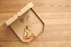 Cardboard box with pizza piece on wooden background. Top view with space for text stock images