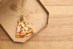 Cardboard box with pizza piece on wooden background, top view. With space for text stock image