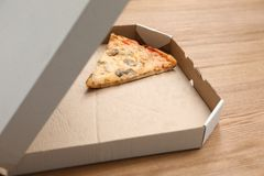 Cardboard box with pizza piece. On wooden table stock photo