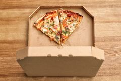 Cardboard box with pizza pieces on wooden background. Top view stock images