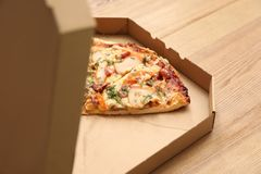 Cardboard box with pizza pieces on wooden table. Space for text royalty free stock photos