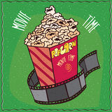 Cardboard box with popcorn and reel of film. Bright cardboard box with heap of popcorn and reel of film. Cinema concept. Green background and lettering Movie Stock Photography