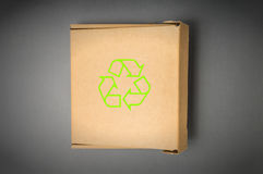 Cardboard box with recycle sign isolated on a gray background. Stock Photos