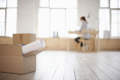 Cardboard Box And Rolled Paper On Floor Of Loft Apartment. Cardboard box and rolled paper on wooden floor with woman in background Stock Photos