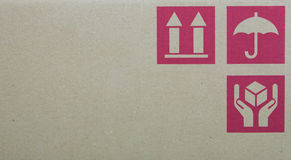 Cardboard box symbols. Fine image close-up of grunge red fragile symbol on cardboard Royalty Free Stock Photo
