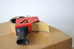 Cardboard box and tape dispenser. Self-adhesive tape dispenser on brown cardboard box Stock Photo