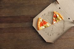 Cardboard box with tasty pizza slices on wooden background, top view. Space for text stock image