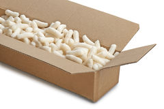 Cardboard box with yellow packing styrofoam peanuts Royalty Free Stock Images