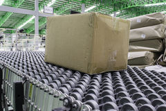Cardboard boxes on conveyor belt in distribution warehouse. Stock Image