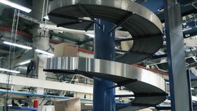 Cardboard boxes on conveyor belt in factory. Clip. Production line on which the boxes move in a spiral Royalty Free Stock Images