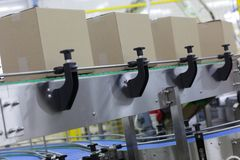 Cardboard boxes on conveyor belt in factory. Grey cardboard boxes on conveyor belt in factory - close up stock images