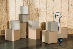 Cardboard boxes and hand truck stock images