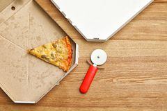 Cardboard boxes, knife and pizza piece on wooden background, top view. With space for text stock photos