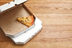 Cardboard boxes and pizza piece on wooden table. Space for text royalty free stock photos