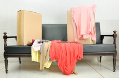 Cardboard boxes and stack of clothes on a sofa Stock Photos