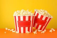 Cardboard buckets tasty popcorn against yellow background