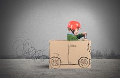 Cardboard car. Creative baby plays with his cardboard car Royalty Free Stock Image