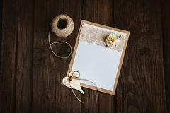 Cardboard card with flower. The basis for the writing on the brown wooden table in retro style hand made paper rose Royalty Free Stock Photo