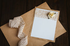 Cardboard card with flower. The basis for the writing on the brown wooden table in retro style hand made paper rose Stock Image