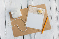 Cardboard card with flower. The basis for writing on a white wooden table in retro style hand made paper rose Stock Image