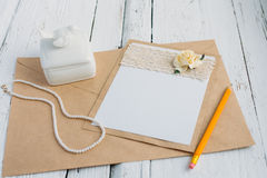 Cardboard card with flower. The basis for writing on a white wooden table in retro style hand made paper rose Stock Photos