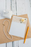 Cardboard card with flower. The basis for writing on a white wooden table in retro style hand made paper rose Royalty Free Stock Image