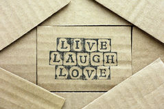 Cardboard card with words Live Laugh Love. Made by black alphabet stamps with piece of cardboard Royalty Free Stock Photo