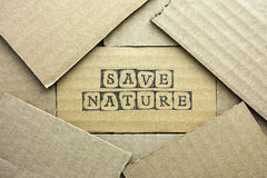 Cardboard card with words Save Nature. Made by black alphabet stamps with piece of cardboard Royalty Free Stock Photo