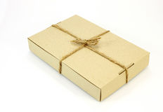 Cardboard carton wrapped with brown paper and tied with cord. On white background royalty free stock image