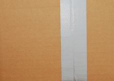 A cardboard with closing tape. Cardboard background with tape tat top box Stock Photo