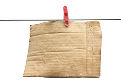 Cardboard with clothes-peg on the wire. Isolated cardboard with clothes-peg on the wire on a white backround Stock Images