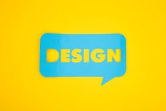 The cardboard cloud with design word. The design word cut-out in the blue colored cardboard bubble on the yellow background royalty free stock image
