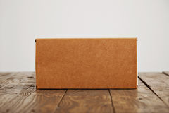 Cardboard craft package box and bag set. Craft blank cardboard package box presented on stressed brushed wooden table, isolated on white background royalty free stock images